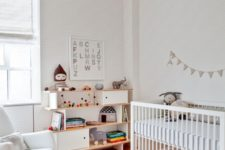 a neutral modern nursery with a rocker chair, a crib, a creative sideboard, rugs and striped walls and a ceiling