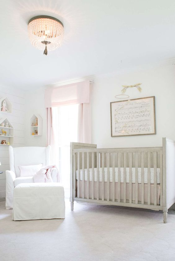 a neutral nursery softened with pinnk curtains, a vintge crib, a white chair with a footrest and house shaped shelves