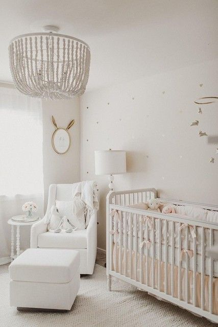 a neutral nursery with a beaded chandelier, a vintage crib, a white chair with a footrest, a mirror and a mobile
