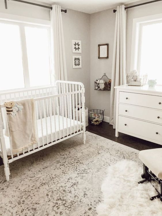 a neutral nursery with a printed rug, white furniture, wire basket shelves and storage units and artworks