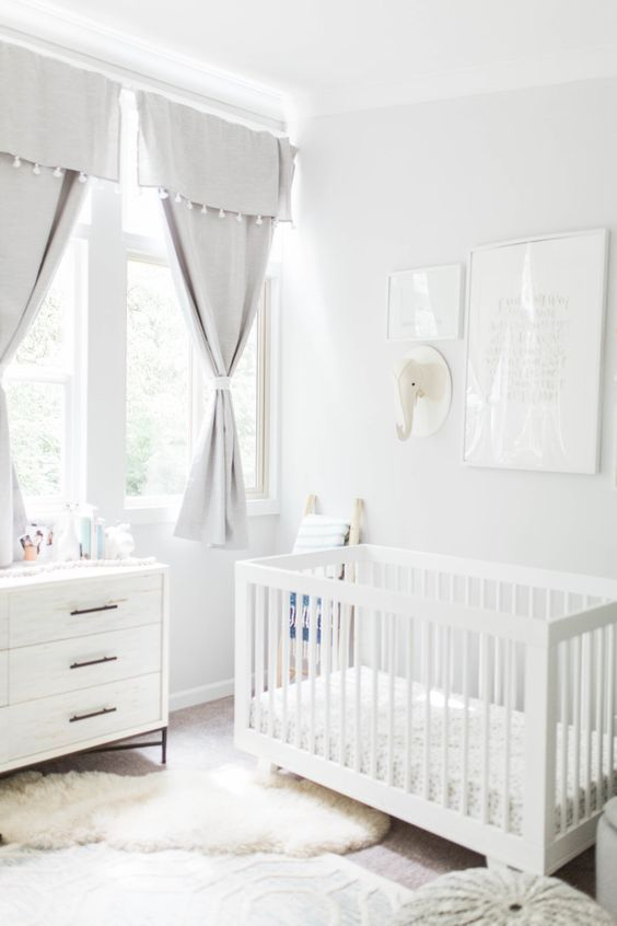 a neutral nursery with grey curtains, white furniture, layered rugs, a gallery wall with a toy head