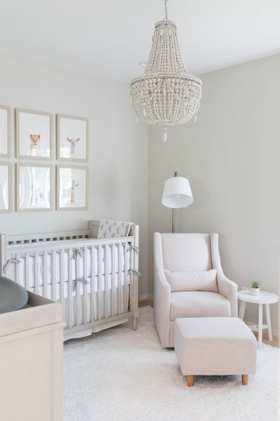 a peaceful nursery with a blush chair and a footrest, a beaded chandelier, a vintage crib and dresser and a gallery wall