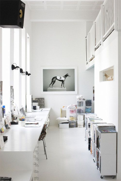 a shared white home office with lots of storage cabinets, a shared desk, some art and lamps and lots of light