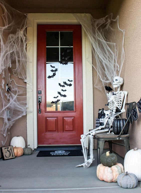 a simple and cool Halloween porch with spiderwebs, a skeleton, blackbirds, heirloom pumpkins and bats on the door