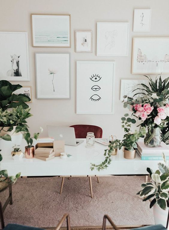 a simple and neutral home office with a neutral gallery wall, potted blooms and greenery and a large white desk