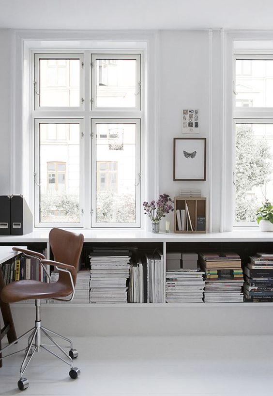 a simple minimalist white home office with a large open storag eunit, a white desk and a brown leather chair