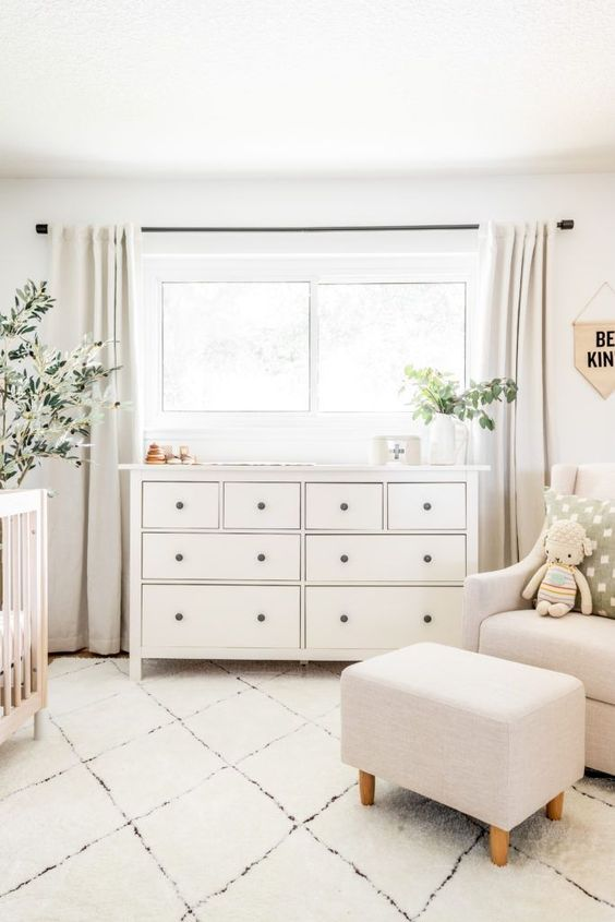 a simple neutral nursery with contemporary neutral furniture, a wooden crib, potted greenery and some toys