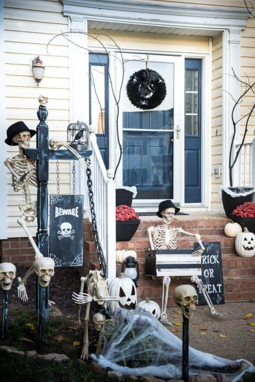 a skeleton porch with several skeletons, skulls, skeleton hands, a black wreath, a sign and spiderwebs looks impressive