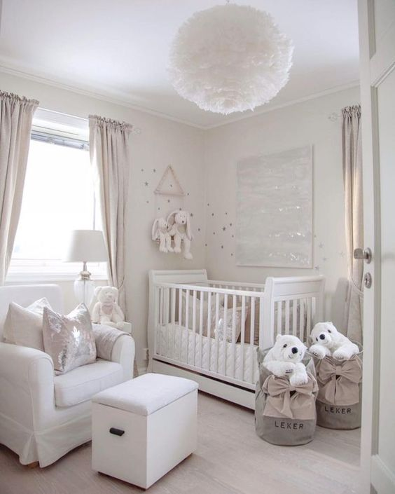 a small neutral nursery with a crib, a white chair and ottoman, baskets with polar bears and a fluffy pendant lamp