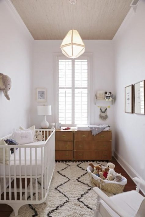 a small neutral nursery with a printed rug, wooden dressers, lots of toys and a faux elephant head on the wall