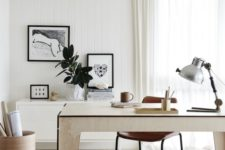 a stylish neutral home office with a plywood desk, a cabinet on the wall, a leather chair, some artworks