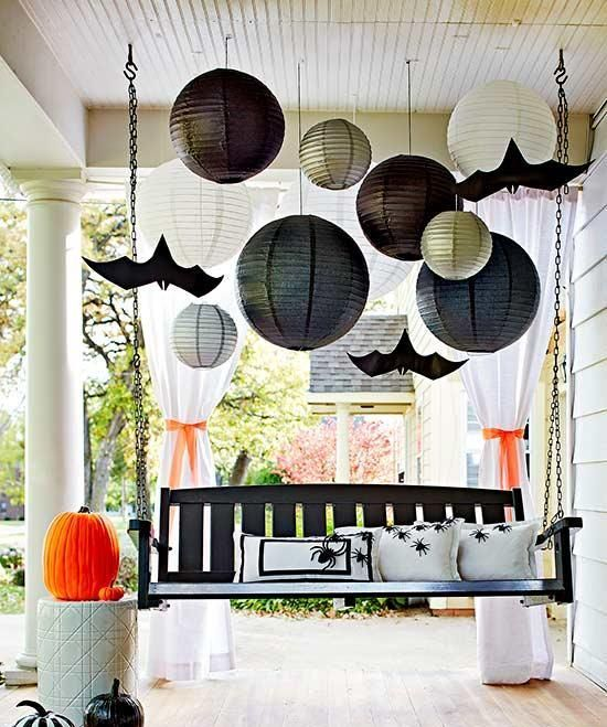 a suspended blakc bench with spider pillows, painted pumpkins, large papper lanterns and paper bats