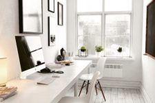 a very neutral and small home office with a shared white desk, white chairs, a gallery wall with art in black frames