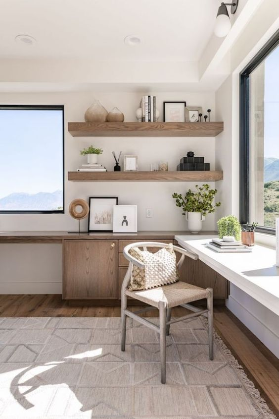 a welcoming neutral home office with amazing views and two desks, wooden shelves and a comfy chair, much natural light