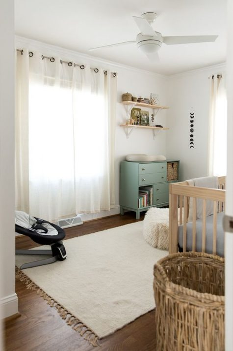 a welcoming neutral nursery with a green changing table, wicker and wooden touches, a neutral rug and a sheer curtain