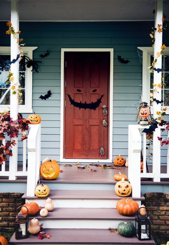 a whimsical Halloween porch with carved pumpkins on steps, candle lanterns, paper bats, fall leaves and a grin door