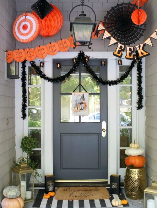 a whimsical Halloween porch with large black and orange paper decorations, natural pumpkins, candle lanterns and greenery