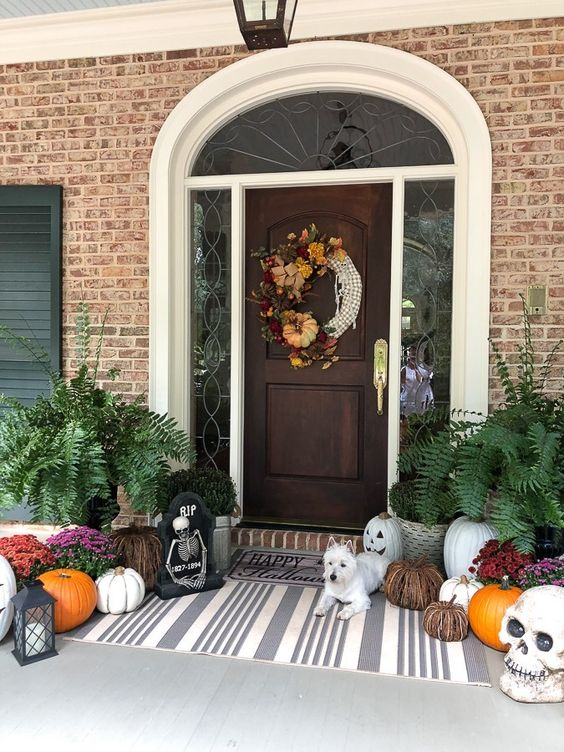 a whimsy Halloween porch with a creative wreath, natural and vine pumpkins, skulls, blooms and greenery