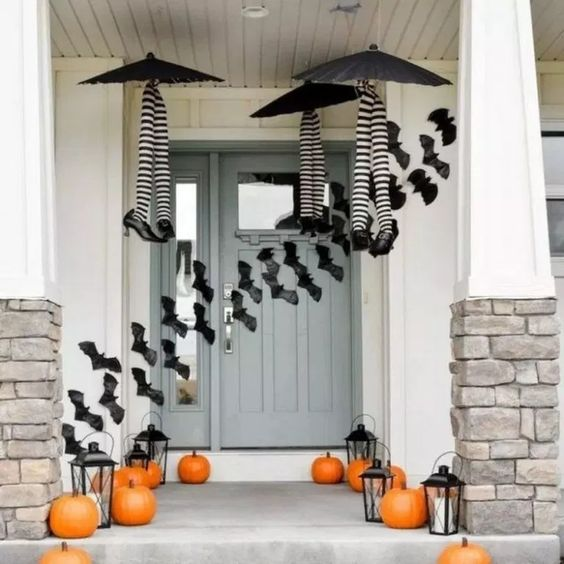 a whimsy Halloween porch with witches' legs and umbrellas, orange pumpkins, candle lanterns and bats