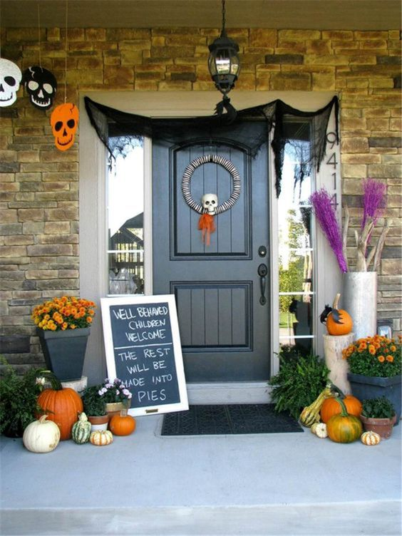 a whimsy and original Halloween porchh with skulls of paper, a skull wreath, natural pumpkins and bold fall blooms