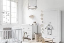an airy neutral nursery with a cool rug, baskets, wooden stools, white storage furniture and a crib and a cool pendant lamp