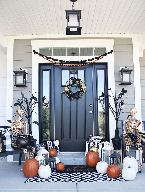an elegant Halloween porch with gilded skeletons, orange and white pumpkins, candle lanterns and a wreath with spiders
