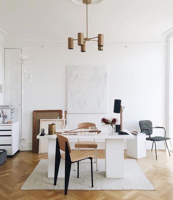 an elegant home office with a wihte desk, plywood chairs, some artworks and bronze touches here and there