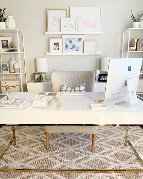 an elegant neutral home office with a large desk, storage units in white, cabinets, a gallery wall on ledges and a comfy chair