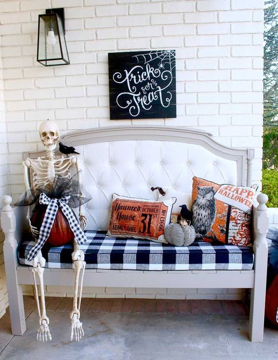an upholstered bench with Halloween pillows, a skeleton with a pumpkin and a bow atop, a sign and a candle lantern