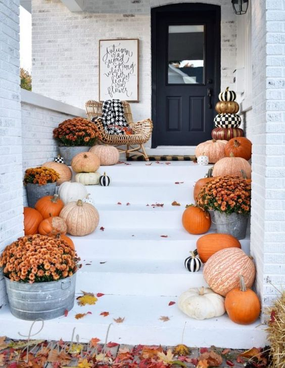 elegant farmhouse porch decor with natural pumpkins, bold fall blooms and touches of black and white for a Halloween feel