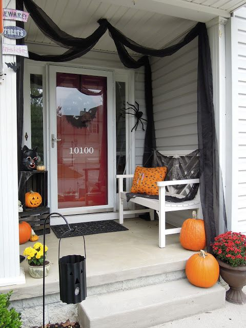 large orange pumpkins, bright fall blooms, spiders and black tulle for simple and fast Halloween porch decor