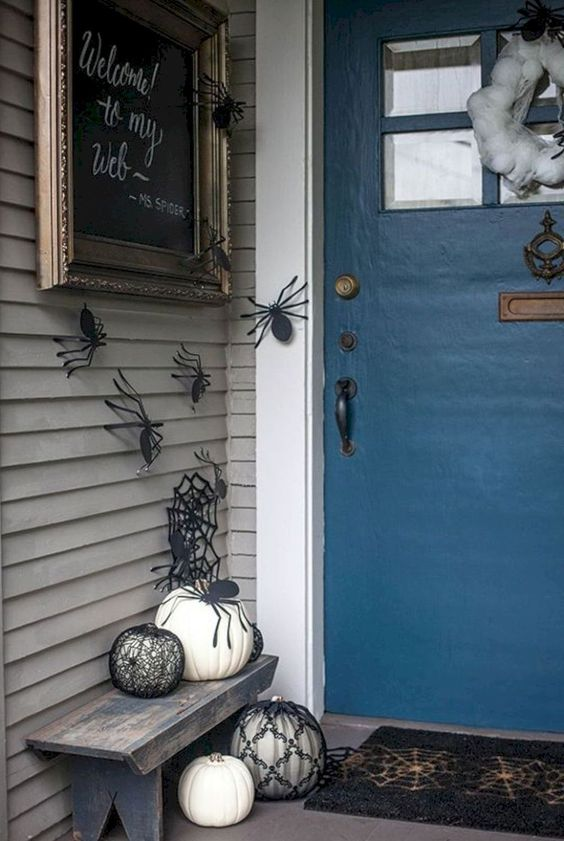 paper spiders on the walls, black and white pumpkins, a spiderweb wreath and a sign for simple and fast Halloween decor