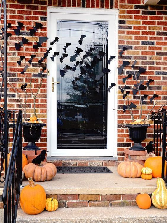 simple and stylish Halloween porch decor with heirloom pumpkins, blackbirds and bats on the walls and door