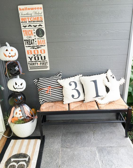 stacked carved pumpkins in a pot, a bench with Halloween pillows, a sign and a mat for Halloween