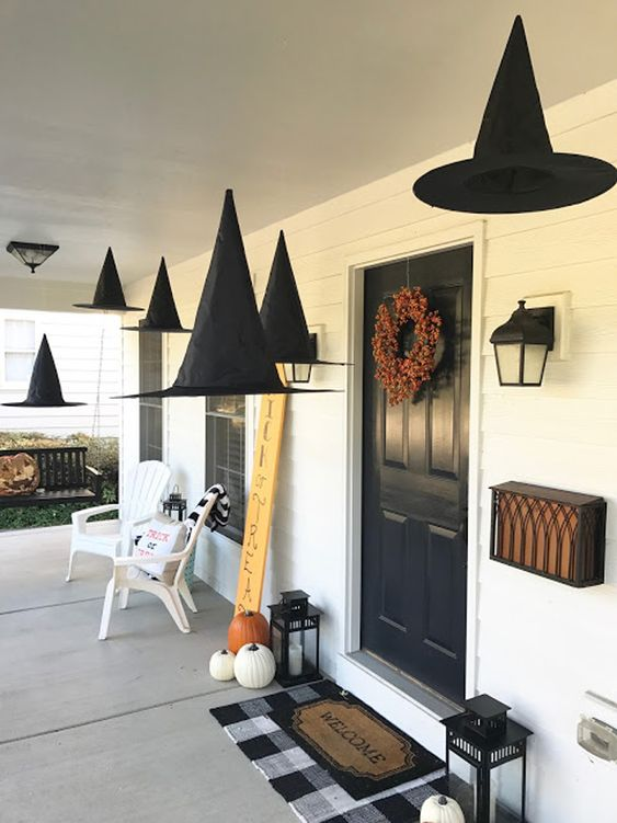 witch hats suspended, natural pumpkins, candle lanterns and a bold fall bloom wreath for a Halloween porch