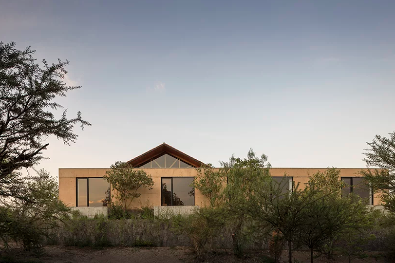 This contemporary home is located in Mexico, it fully adapts to the terrain and merges with nature with its earthy colors