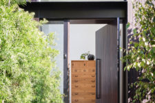 02 The front door is clad with dark wood and it's pivoting, which gives a modern feel to the space