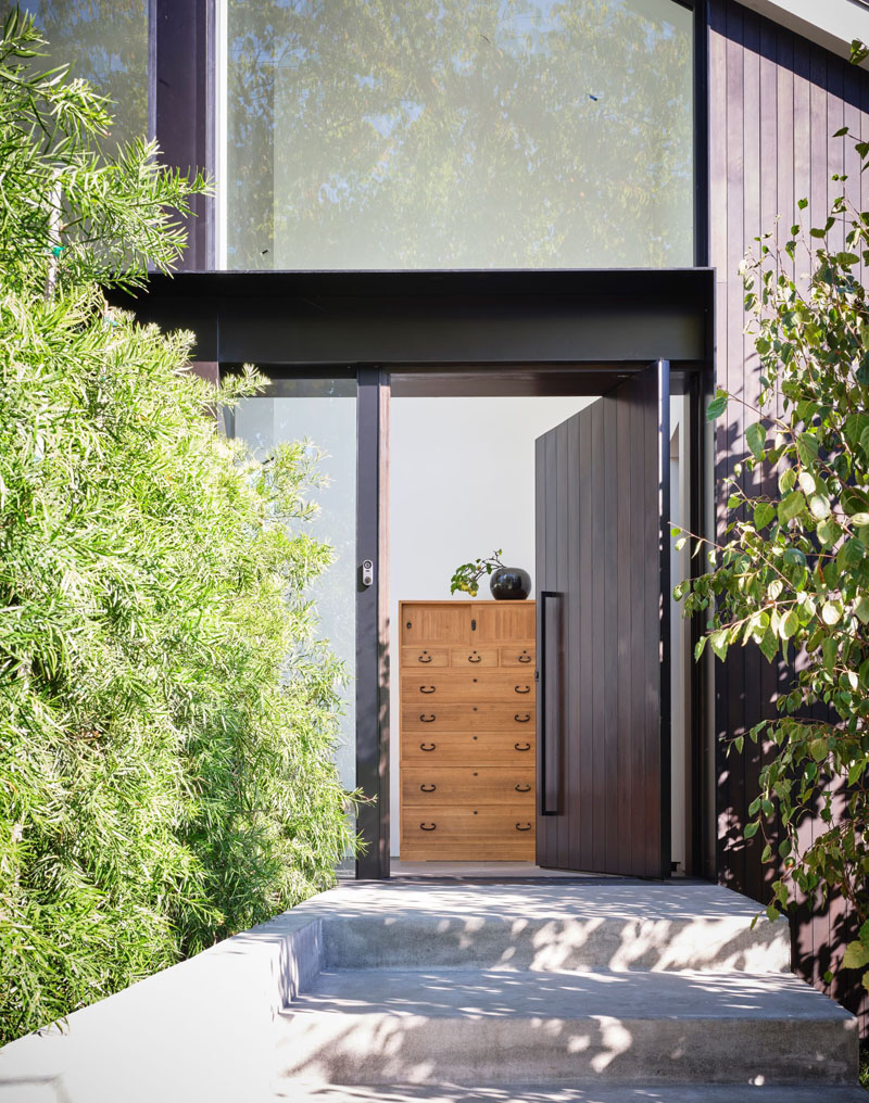 The front door is clad with dark wood and it's pivoting, which gives a modern feel to the space