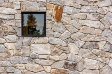 02 The house is clad with locally-sourced wood and stone, which help it blend with the surroundings