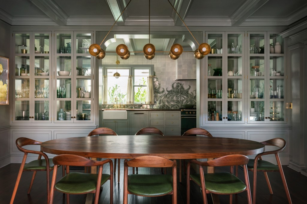 The kitchen and dining space are divided with large storage units and the green chairs add color