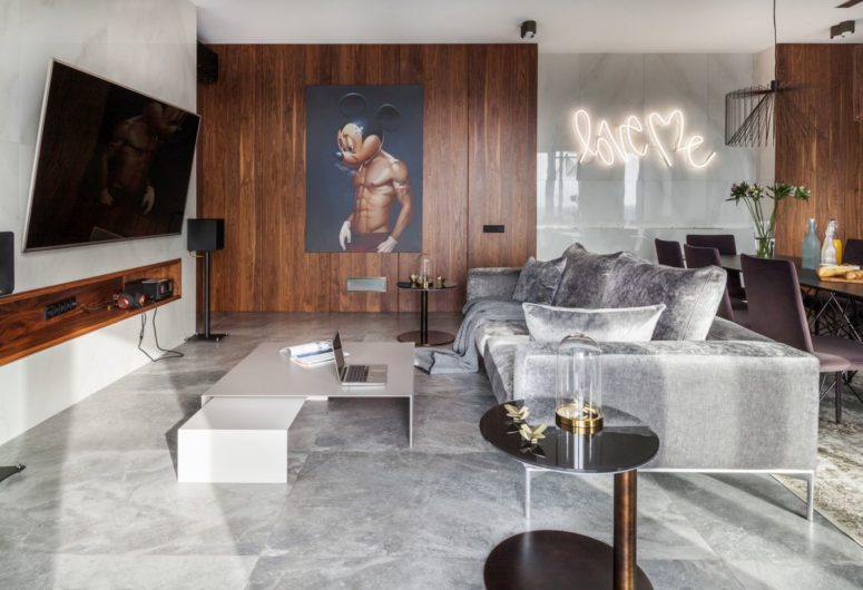 The living area is done with marble tiles, neutral furniture, a whimsy art and a large TV