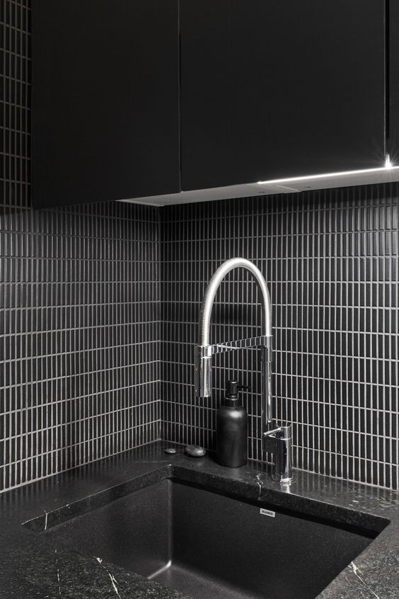 a black minimalist backsplash with narrow tiles placed vertically and highlighted with white grout