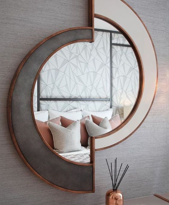 a chic sculptural mirror in white and grey, with copper framing is a beautiful decoration that will add light
