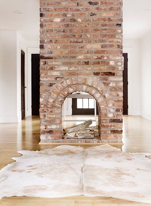 a gorgeous double-sided fireplace clad with brick looks very vintage and brings a character and a story to the room