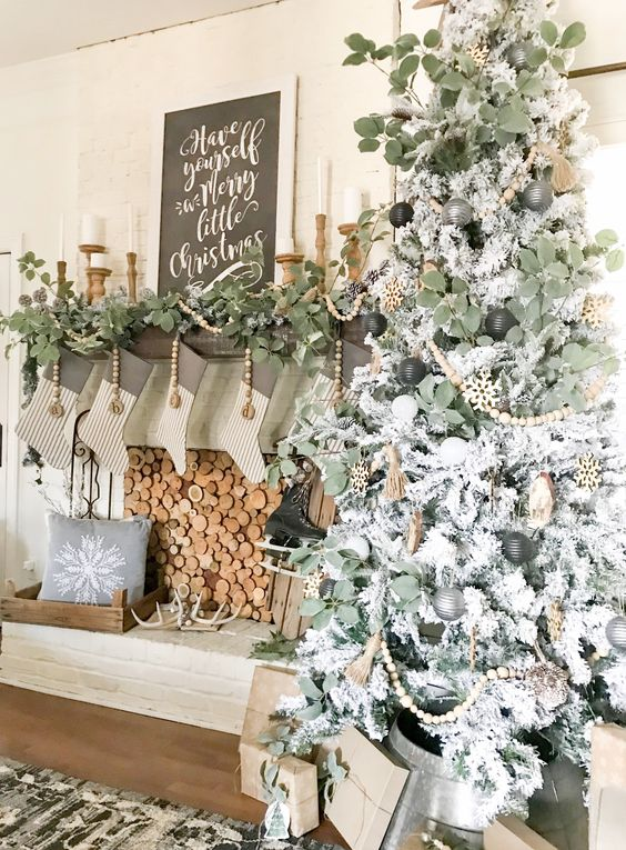 a neutral Christmas tree with black, grey and white ornaments and wooden beads, a fireplace with greenery and wooden beads, striped stockings and antlers
