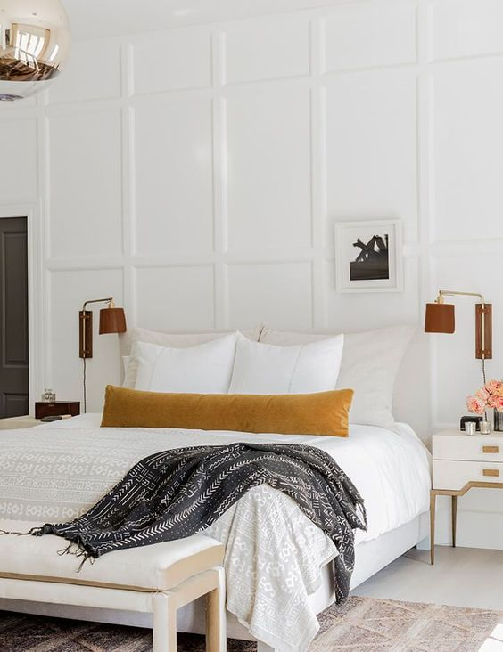 a neutral bedroom with paneling, chic neutral furniture, elegant leather sconces and a printed rug looks welcoming