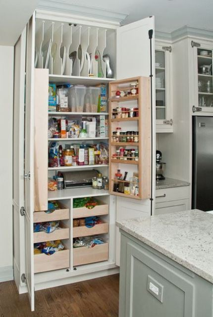 a neutral kitchen with a built in pantry with lots of various shelves and drawers to store everything you may need