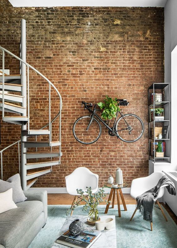 an exposed brick wall with a bike shelf on it is a great industrial touch to this contemporary space