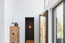 03 The foyer is light-colored and there's a stylish light-colored woodne cabinet that feels very vintage-like
