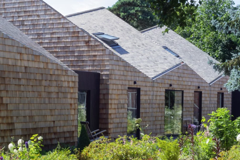 The house is fully clad with shingles and it looks like a fresh take on a traditional barn, with sculptural shapes